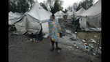 A migrant stands in the Vucjak refugee camp outside Bihac, northwestern Bosnia, Thursday, Nov. 14, 2019. The European Union's top migration official is warning Bosnian authorities of a likely humanitarian crisis this winter due to appalling conditions in overcrowded migrant camps in the country. (AP Photo/Darko Vojinovic)