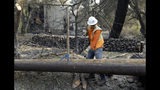FILE - In this Oct. 18, 2017, file photo, a Pacific Gas & Electric worker replaces power poles destroyed by wildfires in Glen Ellen, Calif. California's Pacific Gas & Electric is faced regularly with a no-win choice between risking the start of a deadly wildfire or immiserating millions of paying customers by shutting off the power. (AP Photo/Ben Margot, file)