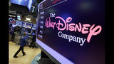 """FILE - In this Aug. 8, 2017, file photo, The Walt Disney Co. logo appears on a screen above the floor of the New York Stock Exchange. Disney's new streaming service, Disney Plus, is adding a disclaimer to """"Dumbo,"""" """"Peter Pan"""" and other classics because they depict racist stereotypes, underscoring a challenge media companies face when they resurrect older movies in modern times. (AP Photo/Richard Drew, File)"""