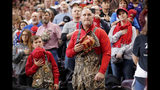 A man and boy dressed in chest waders hold their hats to their hearts during the Pledge of Allegiance at the start of a campaign rally for President Donald Trump in Bossier City, La., Thursday, Nov. 14, 2019. (AP Photo/Gerald Herbert)