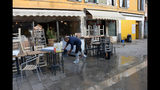 A man cleans up following a flooding in Venice, Italy, Thursday, Nov. 14, 2019. The worst flooding in Venice in more than 50 years has prompted calls to better protect the historic city from rising sea levels as officials calculated hundreds of millions of euros in damage. The water reached 1.87 meters above sea level Tuesday, the second-highest level ever recorded in the city. (Andrea Merola/ANSA via AP)