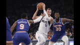 Dallas Mavericks' Kristaps Porzingis (6) drives past New York Knicks' RJ Barrett (9) and Julius Randle (30) during the first half of an NBA basketball game Thursday, Nov. 14, 2019, in New York. (AP Photo/Frank Franklin II)