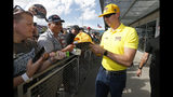 Driver Kyle Busch, right, gives autographs to fans prior to a NASCAR Cup Series auto race at ISM Raceway, Sunday, Nov. 10, 2019, in Avondale, Ariz. (AP Photo/Ralph Freso)