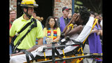 FILE - In this Aug. 12, 2017, file photo, an emergency employee helps an injured person after a neo-Nazi drove his car into a group of counter-protesters at a white nationalist rally in Charlottesville, Va. A group of plaintiffs has filed a lawsuit alleging that individuals who planned the rally conspired to infringe on their civil rights. (AP Photo/Steve Helber, File)