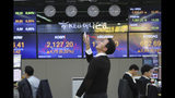 A currency trader uses a remote control to adjust temperature on an overhead air-conditioner at the foreign exchange dealing room of the KEB Hana Bank headquarters in Seoul, South Korea, Thursday, Nov. 14, 2019. Asian stock markets were mixed Thursday amid doubts about the status of a U.S.-Chinese trade deal after the U.S. Federal Reserve's chairman said it is likely to leave its benchmark interest rate unchanged. (AP Photo/Ahn Young-joon)