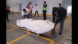 Airport workers prepare to upload the coffin of former British army officer James Le Mesurier onto a cargo plane prior to his repatriation at Istanbul Airport, Wednesday, Nov. 13, 2019. Turkey's state-run Anadolu news agency says the body of Le Mesurier who co-found the White Helmets volunteer group in Syria, has been transferred to Istanbul's main airport to be flown to London, following an autopsy. (IHA via AP)