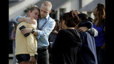 D.J. Hamburger, center in blue, a teacher at Saugus High School, comforts a student after reports of a shooting at the school on Thursday, Nov. 14, 2019, in Santa Clarita, Calif. (AP Photo/Marcio Jose Sanchez)