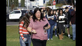 Students are escorted in a single file line as some parents pick them up outside of Saugus High School after reports of a shooting on Thursday, Nov. 14, 2019, in Santa Clarita, Calif. (AP Photo/Marcio Jose Sanchez)