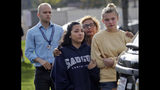 People wait outside of Saugus High School after reports of a shooting on Thursday, Nov. 14, 2019, in Santa Clarita, Calif. Los Angeles County Sheriff Alex Villanueva tweeted that the suspect was in custody and was being treated at a hospital. He said the suspect was a student but gave no further information.(AP Photo/Marcio Jose Sanchez)