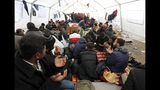 """Migrants pray in the Vucjak refugee camp outside Bihac, northwestern Bosnia, Friday, Nov. 15, 2019. The European Union's top migration official has joined the calls for the closure of a migrant camp in Bosnia set up on a former landfill. The EU has given Bosnia over 36 million euros ($40 million) in aid. But conditions at Vucjak are so bad that the EU's migration commissioner says that """"no EU financial support can, or will be, provided for it."""" (AP Photo/Darko Vojinovic)"""