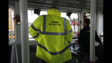 """Britain's Prime Minister Boris Johnson wears safety clothing reading """"Prime Minister"""" during a General Election campaign stop aboard a tog boat in the port of Bristol, England, Thursday, Nov. 14, 2019. Britain goes to the polls on Dec. 12. (AP Photo/Frank Augstein, Pool)"""