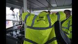 """Britain's Prime Minister Boris Johnson dons safety clothing reading """"Prime Minister"""" during a General Election campaign stop aboard a tog boat in the port of Bristol, England, Thursday, Nov. 14, 2019. Britain goes to the polls on Dec. 12. (AP Photo/Frank Augstein, Pool)"""