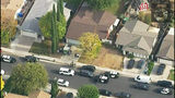 This photo from video provided by KTLA-TV shows police vehicles filling the street in front of the home of the alleged shooter, with the brown roof at center, after a shooting at Saugus High School in Santa Clarita, Calif., early Thursday, Nov. 14, 2019. (KTLA-TV via AP)