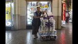 In this Nov. 5, 2019 photo, retired Maria Gonzalez, 77, poses for a photo as she takes a break from selling tissue and toilet paper in downtown Santiago, Chile. Gonzalez says she is tired of waking up, Monday to Friday, to sell toilet paper in the Chilean capital. Her meager $146 monthly pension puts her below the poverty line, which in Chile is around $222 a month. (AP Photo/Esteban Felix)