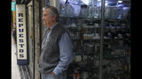 In this Nov. 4, 2019 photo, retired Jose Urzua, 74, poses for a photo at his work at a store that sells spare parts for blenders, in downtown Santiago, Chile. The protests in Chile include struggling retirees as well as others seeking better salaries, subsidized housing, a decrease in the cost of medicine and a new constitution. (AP Photo/Esteban Felix)