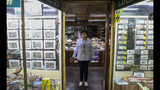 In this Nov. 4, 2019 photo, retired Rosa Lara, 74, poses for a photo inside a philately store in downtown of Santiago, Chile. The protests in Chile include struggling retirees as well as others seeking better salaries, subsidized housing, a decrease in the cost of medicine and a new constitution. Many also want to overhaul a dictatorship-era private pension system that is widely criticized in a country with a rapidly aging population. (AP Photo/Esteban Felix)
