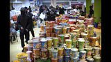 Protesters walk past stacks of instant noodles in a canteen at Hong Kong Polytechnic University in Hong Kong, Friday, Nov. 15, 2019. Protesters who have barricaded themselves in a Hong Kong university partially cleared a road they were blocking and demanded that the government commit to holding local elections on Nov. 24. (AP Photo/Vincent Yu)