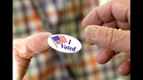 """FILE - In this Tuesday, Nov. 5, 2019 file photo, a poll worker offers a voter an """"I Voted"""" sticker after casting a ballot in Ridgeland, Miss. On Friday, Nov. 15, 2019, The Associated Press reported on a video circulating online incorrectly asserting that a rigged voting machine in Mississippi switched the vote to Lt. Gov. Tate Reeves after a voter selected Bill Waller Jr. in the Republican primary runoff for governor. The Mississippi Secretary of State's issued a press release on August 27, explaining that the video showed a machine malfunction at the Burgess precinct in the city of Oxford, and the machine was replaced after the issue was discovered. (AP Photo/Rogelio V. Solis)"""