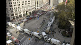 """FILE - In this Monday, Nov. 11, 2019 file photo, sanitation and other utility trucks block off the streets around Madison Square Park as crowds and protesters gather for President Donald Trump's address to kick off the New York City's 100th annual Veterans Day parade in New York. On Friday, Nov. 15, 2019, The Associated Press reported on stories circulating online incorrectly asserting that sanitation trucks surrounding Madison Square in New York were lined up to protect Trump against booing protesters. Officials with the New York City Police Department and the Department of Sanitation confirmed that sanitation trucks are often used for security at big events. They are """"part of our counterterrorism overlay, not unique to this visit,"""" Lt. Eugene Whyte, of the NYPD's public information office, told the AP. (Judy Wolfe via AP)"""
