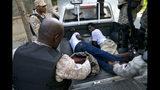 En esta imagen, tomada el 10 de noviembre de 2019, agentes de policía detienen a dos hombres por el supuesto robo de una batería durante una protesta para exigir la renuncia del presidente Jovenel Moise, en Puerto Príncipe, Haití. El malestar por la corrupción, la inflación y la escasez de productos básicos, incluyendo combustible, derivó en más de un mes de movilizaciones que paralizaron la nación mientras los manifestantes exigen la marcha de Moise. (AP Foto/Dieu Nalio Chery)