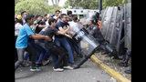 En esta imagen, tomada el 14 de noviembre de 2019, estudiantes universitarios intentan arrebatarle el escudo protector a un miembro de la Policía Nacional Bolivariana durante enfrentamientos en el exterior de la Universidad Central de Venezuela, en Caracas, Venezuela. (AP Foto/Ariana Cubillos)