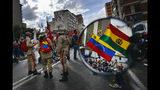 En esta imagen, tomada el 11 de noviembre de 2019, el reflejo de un espejo de una motocicleta muestra a partidarios del presidente de Venezuela, Nicolás Maduro, manifestándose en favor del exmandatario de Bolivia, Evo Morales, en Caracas, Venezuela, tras su dimisión. (AP Foto/Matías Delacroix)