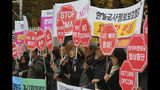 """Protesters stage a rally to oppose a visit by U.S. Secretary for Defense Mark Esper in front of the Defense Ministry in Seoul, South Korea, Friday, Nov. 15, 2019. The sign reads """"We demand to abolish the General Security of Military Information Agreement, or GSOMIA, an intelligence-sharing agreement between South Korea and Japan."""" (AP Photo/Ahn Young-joon)"""