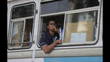 A Sri Lankan polling worker sits in a bus transporting polling material, outside a material distribution center in Colombo, Sri Lanka, Friday, Nov. 15, 2019. Worries about Islamic extremism will be paramount for many Sri Lankan voters while others hope to block former leaders accused of human rights violations from returning to power in Saturday's presidential election, the country's first national polls since last Easter's deadly suicide attacks. (AP Photo/Eranga Jayawardena)