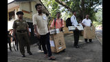 Sri Lankan police officers and polling workers wait to set off for their respective polling stations outside a material distribution center in Colombo, Sri Lanka, Friday, Nov. 15, 2019. Worries about Islamic extremism will be paramount for many Sri Lankan voters while others hope to block former leaders accused of human rights violations from returning to power in Saturday's presidential election, the country's first national polls since last Easter's deadly suicide attacks. (AP Photo/Eranga Jayawardena)