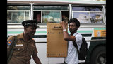 A Sri Lankan polling worker carries ballot papers and boxes to a bus outside a material distribution center as they transport them to polling centers in Colombo, Sri Lanka, Friday, Nov. 15, 2019. Worries about Islamic extremism will be paramount for many Sri Lankan voters while others hope to block former leaders accused of human rights violations from returning to power in Saturday's presidential election, the country's first national polls since last Easter's deadly suicide attacks. (AP Photo/Eranga Jayawardena)