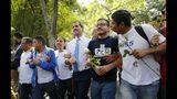 El líder de la oposición de Venezuela, Juan Guaidó (centro), que se autoproclamó presidente interino del país, camina con estudiantes en la Universidad Central de Venezuela tras reunirse con ellos, en Caracas, Venezuela, el 14 de noviembre de 2019. El gobierno y la oposición han convocado a marchas el sábado 16 de noviembre de 2019. (AP Foto/Ariana Cubillos)