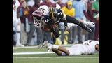 Iowa wide receiver Tyrone Tracy, center, dives for more yards as he is tackled by Minnesota linebacker Mariano Sori-Marin, left, during the first half of an NCAA college football game, Saturday, Nov. 16, 2019, in Iowa City, Iowa. (AP Photo/Matthew Putney)