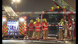 """Fire fighters at the scene of a major fire at a student residential building in Bolton, England, late Friday Nov. 15, 2019. Fire crews tackled the large blaze described by an eye witness as """"crawling up the cladding"""" of a student accommodation building, with students evacuated but still being accounted for Saturday morning. (Peter Byrne/PA via AP)"""