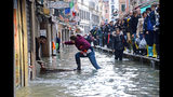 A woman tries to cross a flooded street as people walk on a trestle bridge during high water, in Venice, northern Italy, Nov. 15, 2019. (Andrea Merola/ANSA via AP)