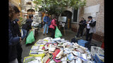 "Damaged books are piled outside renowned bookstore ""Acqua Alta"" (High Water) as volunteers help cleaning after flooding in Venice, Italy, Saturday, Nov. 16, 2019. High tidal waters returned to Venice on Saturday, four days after the city experienced its worst flooding in 50 years. Young Venetians are responding to the worst flood in their lifetimes by volunteering to help salvage manuscripts, clear out waterlogged books and lend a hand where needed throughout the stricken city.(AP Photo/Luca Bruno)"