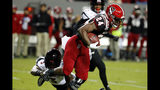North Carolina State's Zonovan Knight (24) tries to break the tackle of Louisville's Russ Yeast (3) during the first half of an NCAA college football game in Raleigh, N.C., Saturday, Nov. 16, 2019. (AP Photo/Karl B DeBlaker)