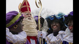 """-FILE- In this Saturday Nov. 16, 2013, image The Dutch version of Santa Claus, Sinterklaas, or Saint Nicholas, and his blackface sidekicks """"Zwarte Piet"""" or """"Black Pete"""" arrive by steamboat in Hoorn, north-western Netherlands. Saint Nicholas is due to arrive in the Netherlands Saturday Nov. 16, 2019, in an annual children's party that has become the backdrop for increasingly acrimonious confrontations between supporters and opponents of his sidekick, Black Pete, a depictions which opponents say promotes racist stereotypes. (AP Photo/Peter Dejong, File)"""