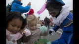"""In this Sunday Nov. 17, 2013, image children get candy from """"Zwarte Piet"""", or Black Pete, the blackface sidekick of the Dutch version of Santa Claus, during a parade in Amsterdam, Netherlands. Saint Nicholas is due to arrive in the Netherlands saturday Nov. 16, 2019, in an annual children's party that has become the backdrop for increasingly acrimonious confrontations between supporters and opponents of his sidekick, Black Pete, a depictions which opponents say promotes racist stereotypes. (AP Photo/Peter Dejong)"""