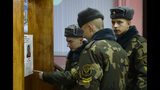 Belarus' Army servicemen examine a list of candidates at a polling station during parliamentary elections in Minsk, Belarus, Sunday, Nov. 17, 2019. (AP Photo/Sergei Grits)