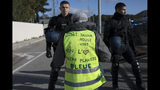 "A yellow vest protester wearing a vest that says ""we love our planet blue"", faces French riot police during a yellow vest demonstration at the l'Étoile road toll lanes marking the one year anniversary of the yellow vest movement near Marseille, southern France, Saturday, Nov. 17, 2019. Some protests have clashed with police as yellow vest protesters are marking a year of protests, seeking what they see as economic justice for the French people with changes in government policies. (AP Photo/Daniel Cole)"