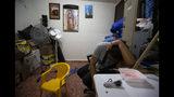 En esta foto del 18 de septiembre de 2019, la esposa del nicaragüense Yohan habla por celular con su familia en Nicaragua desde la cocina de un albergue para migrantes en Monterrey, México. La familia de Linda abandonó su país cuando los paramilitares se enteraron de que su esposo fue testigo del asesinato de un opositor a manos de funcionarios del gobierno. (AP Foto/Fernando Llano)