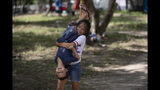 En esta imagen del 11 de octubre de 2019, niños migrantes juegan en una zona donde otros migrantes levantaron un campamento, cerca del puente fronterizo de Matamoros, en México, un punto legal de entrada a Estados Unidos. En años anteriores, los migrantes pasaban con rapidez por esta tierra de cárteles. Ahora, con las nuevas políticas migratorias de Donald Trump, se quedan ahí durante meses mientras esperan sus citas en las cortes estadounidenses, varados en las fauces del crimen organizado. (AP Foto/Fernando Llano)