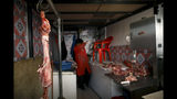 Meat hangs on a butcher shop at a market in La Paz, Bolivia, Monday, Nov. 18, 2019. The blockades of supporters of former president Evo Morales on the outskirts of the main cities of Bolivia are causing a shortage of gasoline and food, which puts pressure on the interim government that seeks to open a dialogue to end four weeks of social and political upheaval. (AP Photo/Natacha Pisarenko)