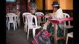 A woman eats at a restaurant in La Paz, Bolivia, Monday, Nov. 18, 2019. The blockades of former president Evo Morales' supporters on the outskirts of the main cities of Bolivia are causing a shortage of gasoline and food. People say markets are short of fruits and vegetables. (AP Photo/Natacha Pisarenko)
