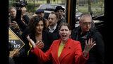 Britain's Liberal Democrats leader Jo Swinson reacts as she is greeted by supporters as she gets off her campaign bus and then stands flanked by Humaira Ali, left, the Liberal Democrats candidate for Southwark and Old Bermondsey as she arrives to campaign at Cafe Amisha in the Southwark and Old Bermondsey constituency in south London, Saturday, Nov. 16, 2019. (AP Photo/Matt Dunham)