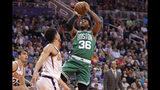 Marcus Smart, base de los Celtics de Boston, dispara frente a Devin Booker, de los Suns de Phoenix, en el encuentro del lunes 18 de noviembre de 2019 (AP Foto/Matt York)