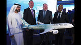 Etihad COO Mohammad al-Bulooki, left, Etihad CEO Tony Douglas, second left, Boeing Commercial Airplanes president and CEO Stanley A. Deal, third left, and Boeing Global Services President and CEO Ted Colbert, right, pose in front of a Boeing 787 Dreamliner model at the Dubai Airshow in Dubai, United Arab Emirates, Monday, Nov. 18, 2019. Abu Dhabi's flagship carrier Etihad said Monday it had partnered with Boeing Co. to launch what they say will be one of the world's most fuel-efficient long haul airplanes as the company seeks to save costs on fuel and position itself as a more environmentally-conscious choice for travelers. (AP Photo/Jon Gambrell)
