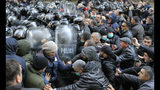 Police push a crowd of demonstrators to clear the area around the Georgian parliament building in Tbilisi, Georgia, Monday, Nov. 18, 2019.Police in riot gear in the country of Georgia are trying to push thousands of demonstrators away from the parliament building in the capital on the second day of sizable protests over the failure of promised election reforms. (AP Photo/Shakh Aivazov)