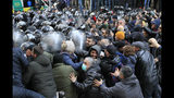 Police push a crowd of demonstrators to clean the area around the Georgian parliament building in Tbilisi, Georgia, Monday, Nov. 18, 2019.Police in riot gear in the country of Georgia are trying to push thousands of demonstrators away from the parliament building in the capital on the second day of sizable protests over the failure of promised election reforms. (AP Photo/Shakh Aivazov)