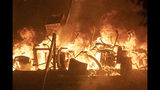 Office chairs burn after police try to storm the Hong Kong Polytechnic University in Hong Kong Monday, Nov. 18, 2019. Fiery explosions were seen early Monday as Hong Kong police stormed into a university held by protesters after an all-night standoff. (AP Photo/Ng Han Guan)